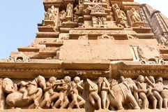 Stone people, horses and elephants on reliefs of Hindu temple in Khajuraho, India. UNESCO Heritage site Stock Photo