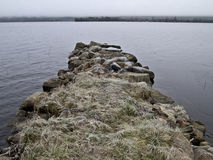 Stone pier. In cold snowy landscape reaches out in the water royalty free stock photography