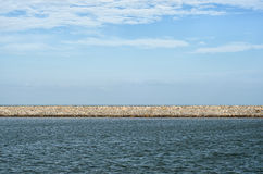 Stone Pier dividing cloudy sky and wavy sea. Natural background Stock Images