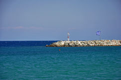Stone pier and Greek flag Royalty Free Stock Images
