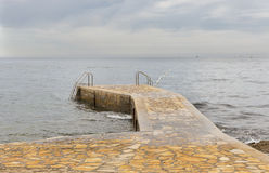 Stone pier with ladders for swimming on a rainy day Royalty Free Stock Photo