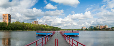 Stone pier at the lake. Panoramic view. High-rise apartment buildings by the lake on a windy day. Picturesque clouds on the blue sky Royalty Free Stock Image