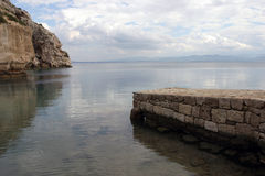 Stone pier and rocks on sea Royalty Free Stock Photos