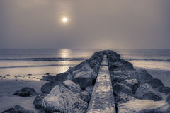Stone pier at sunrise. Pier and ocean at sunrise stock images