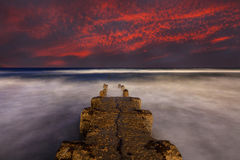Stone pier at sunset Stock Photo