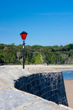 Stone Pier with Vibrant Red Lamp and Blue Sky Stock Photography