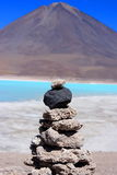 Stone pile. Close up on stone pile with turquoise lake and volcano Licancabur in background Stock Photo