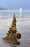 Stone pile at lake tegernsee, sailboat Stock Photography