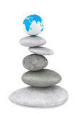 Stone pile in a Zen Garden with a Earth globe. On a white background Royalty Free Stock Image