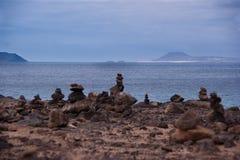 Stone piles in playa blanca. Rock piles in playa blanca with fuerteventura island in the background Stock Photos