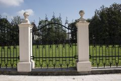 Stone pillar and decorative wrought iron fence gate Royalty Free Stock Image