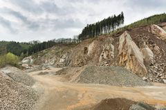 Stone Pit in the Ardennes, Belgium. A large stone pit in the Ardennes, Belgium with dark clouds, a rest of forest on the hill top Royalty Free Stock Photo