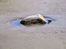 Stone in pool of water on beach stock photo