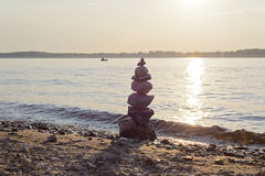 Stone pyramid. Balanced rock cairn built by tourists on the shore of the most majestic rivers of Russia. Photographed at sunset. Samara, Russia, August 4, 2016 Stock Photos