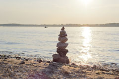 Stone pyramid. Balanced rock cairn built by tourists on the shore of the most majestic rivers of Russia. Photographed at sunset. Samara, Russia, August 4, 2016 Royalty Free Stock Photo