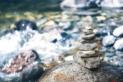 Stone pyramid cairn near river, buddhism Stock Photo
