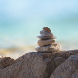 Stone pyramid on the rock on the beach Stock Image