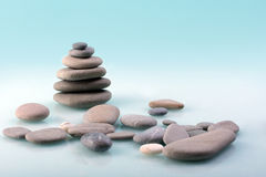 Stone pyramid. Pyramid from sea stones on a turquoise background Royalty Free Stock Image