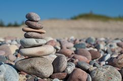 Stone Pyramid. Stacked small stones on the stone beach at summer stock image