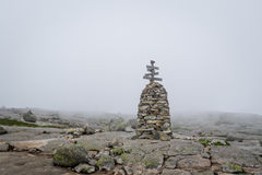 Stone pyramide with hiking path route sign in the foggy weather. Stock Images