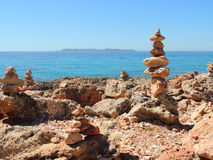 Stone Pyramids on The Beach of Cape Salines, Mallorca Island. Little sculptures - pyramids of red stones mark Cap de ses Salines - the most Southern point of Stock Photo