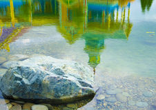 Stone and reflections in the water. Stone and beautiful reflection in the water of the lake Stock Photo