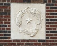 Stone relief panel featuring three fish circling around the Star of Texas on a building in downtown Dallas, Texas.