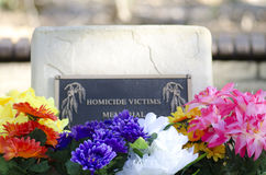 Stone of remembrance in cemetery. A memorial stone for homicide victims in a cemetery, with colourful flowers in the foreground, blurred background and copy stock photography
