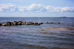A stone ridge peeps out of the water in the sea bay, large waves of tide, cumulus clouds on the horizon Stock Photo