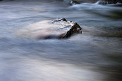 Stone in a river with fast moving water around Royalty Free Stock Images