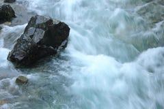 Stone in river stream. Black stone in river stream Royalty Free Stock Photo