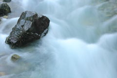 Stone in river stream. Taken with long exposure Stock Photo