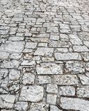Stone road close up. Old pavement of granite. Grey cobblestone sidewalk. Mock up or vintage grunge texture. Template stock photos