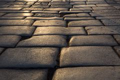 Stone road under sunset. Stone array in the road, textures in details under evening sunshine Stock Photos