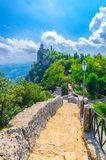 Stone road to Seconda Torre La Cesta Republic San Marino second fortress tower with brick walls on Mount Titano. Rock with green trees, blue sky white clouds royalty free stock image