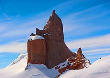 Stone rock in Antarctica on a background of blue sky and snow. royalty free stock image
