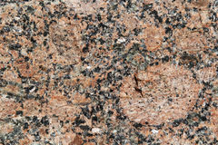 Stone rock red facets a background. Natural background from red coarse-grained granite royalty free stock images