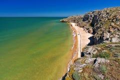 Stone rock on a sandy seashore. And blue sky royalty free stock photos
