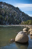Stone rocks on the shore of a mountain river, lake. Blue sky. Royalty Free Stock Images