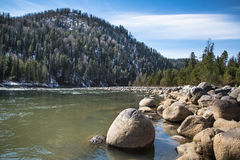 Stone rocks on the shore of a mountain river, lake. Blue sky. Royalty Free Stock Photos