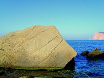 Stone on a rocky seashore. Summer blue sea with a stone in the water. Stock Photo