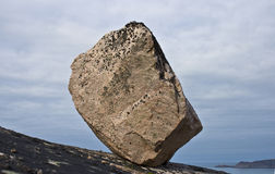 Stone on rocky slope. Big stone standing on a sloping surface close to sea shore Stock Image