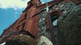 Stone roman catholic church with Jesus on cross. Ancient architecture. In gothic revival style. Great cathedral building in daylight. Old christian temple stock footage