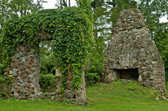 Stone ruins. Wall and fireplace of the ruins of an old stone house Stock Photos