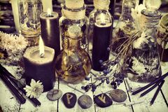 Stone runes with black candles and magic herbs on witch table, toned image. Occult, esoteric, divination and wicca concept. Alternative medicine and Halloween stock photos