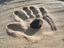 Stone in the Sand Hand Royalty Free Stock Photography
