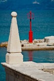 Stone sculpture. With carved main cathedral of Supetar marking with blue sea and red lighthouse in background Royalty Free Stock Photos