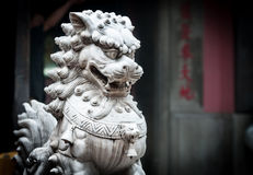Stone sculpture of dragon in buddhist temple. Sculpture of dragon with furious face in buddhist temple, gray wall with characters in background. White stone Royalty Free Stock Photo