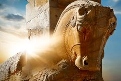 Stone sculpture of a horse in Persepolis against a sunrise. Iran. Persia. Shiraz. Rays of lights Royalty Free Stock Image