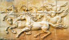 Stone sculpture of horse on wall Stock Photography